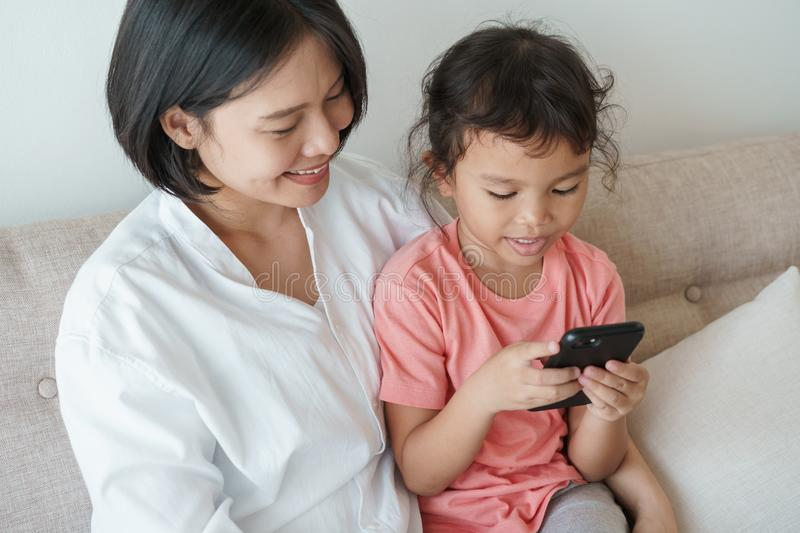 Parent and daughter are using the phone to watch online media stock images