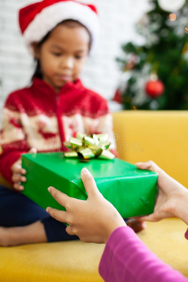 Parent giving Christmas gift box to asian child girl on Christmas celebration. Parent giving Christmas gift box to cute asian child girl on Christmas celebration royalty free stock photos