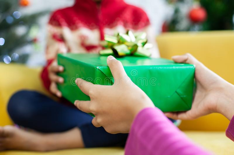 Parent giving Christmas gift box to asian child girl on Christmas celebration. Parent giving Christmas gift box to cute asian child girl on Christmas celebration royalty free stock photography