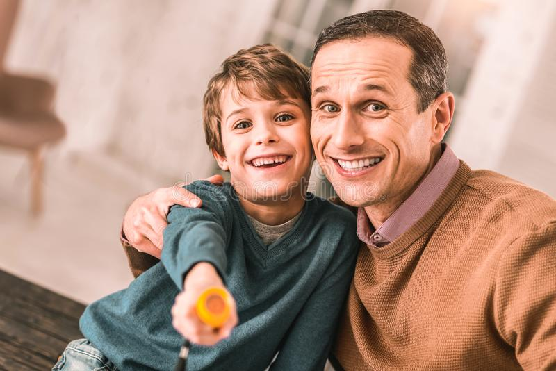 Parent heureux et enfant de sourire posant heureusement pour l'image tout en étreignant images stock