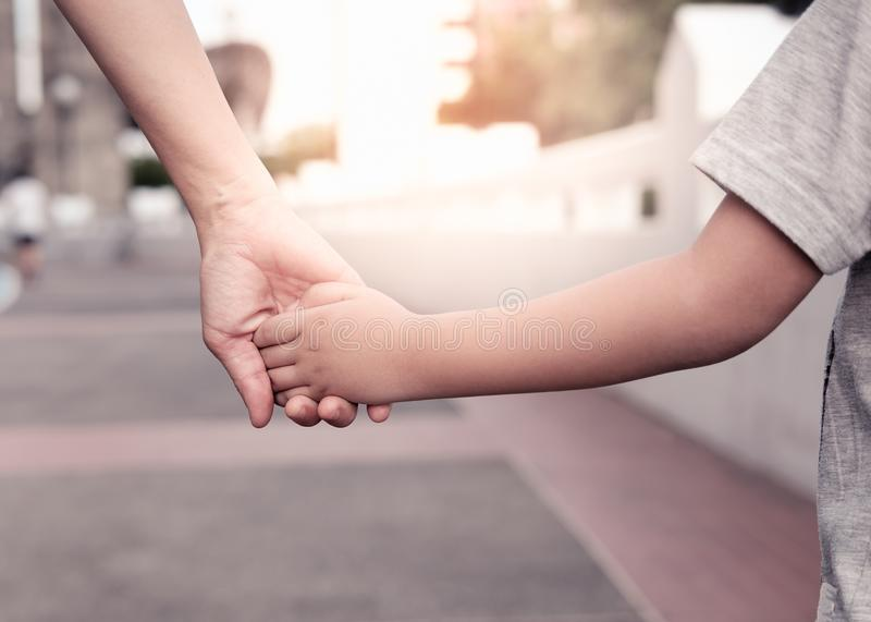 A parent holds the hand of a small boy royalty free stock images