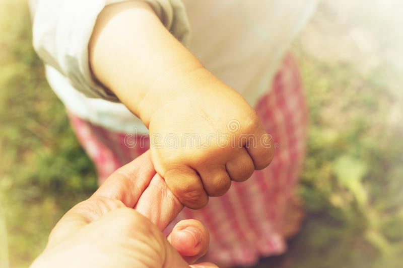 Parent holds the hand of a small child. Toned stock photos
