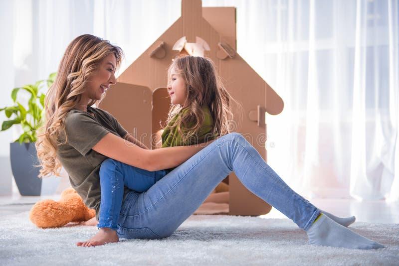Parent joyeux et enfant jouant près de la maison de jouet images stock
