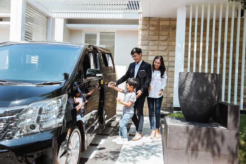 Parent with kid in front of their car smiling royalty free stock photos