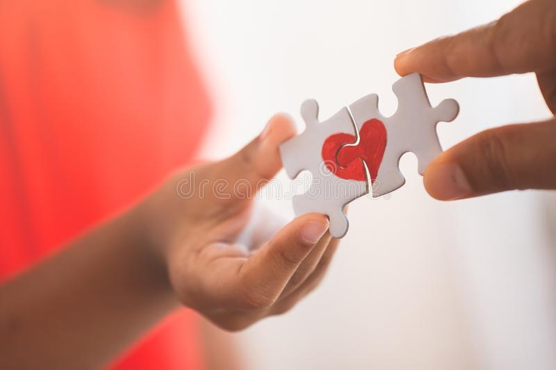 Parent and kid hands connecting couple jigsaw puzzle with drawn red heart. Parent and kid hands connecting couple jigsaw puzzle piece with drawn red heart stock image