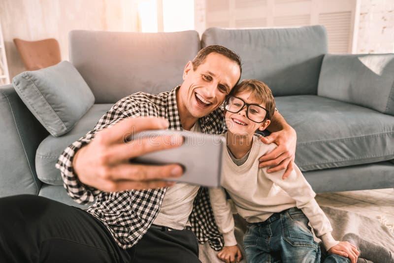 Parent responsable prenant un moment pour se reposer et étreignant son fils photos stock