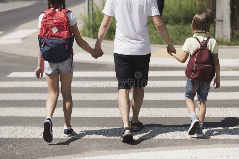 Parent responsable tenant des mains des enfants photos stock
