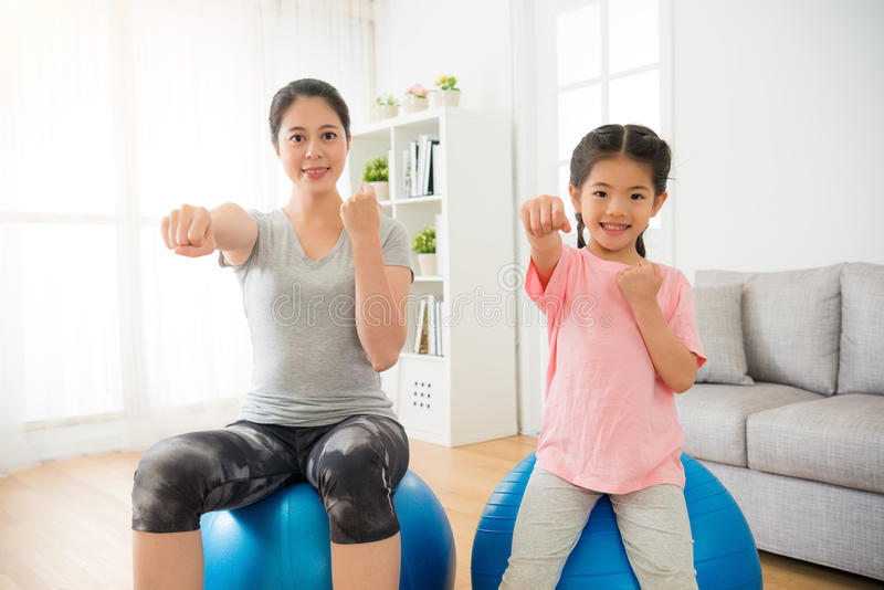 Parent sporting with children showing fist. Parent sporting with children in the living room sitting on the ball and showing fist punch fighting front and doing stock photos