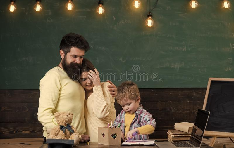 Parent support concept. Parents watching their son drawing, learning to write, chalkboard on background. Boy on busy. Face drawing or writing. Proud parents stock photography