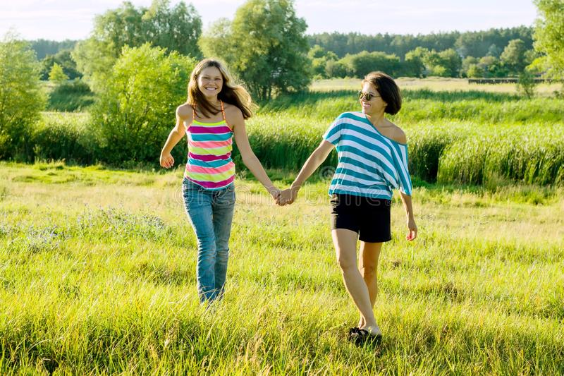 Parent and teenager, Happy mother and teen daughter 13, 14 years old hold hands go laugh talk. Background nature, park royalty free stock photo