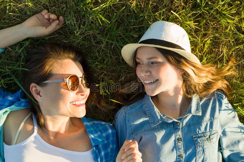The parent and teenager, mom and 14 year old daughter are smiling lying on the green grass. view from above stock photo