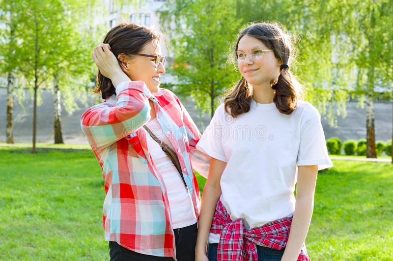 Parent and teenager, mother talks with her teen daughter 13, 14 years old. Background nature, park.  stock image
