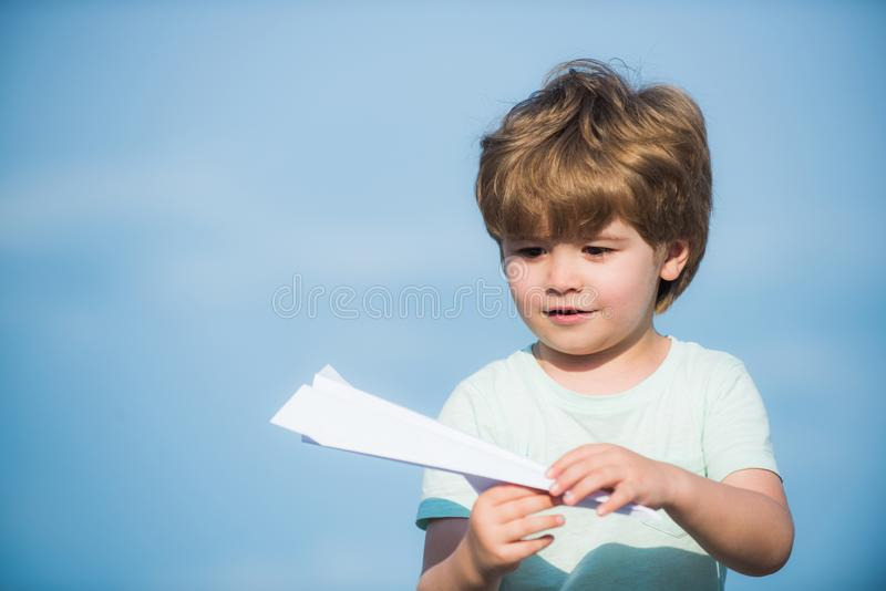 Parenthood and childhood concept. Dreams of traveling. Happy kid on summer field - dream of flying concept. Happy child. Cute boy with paper aipplene royalty free stock photography