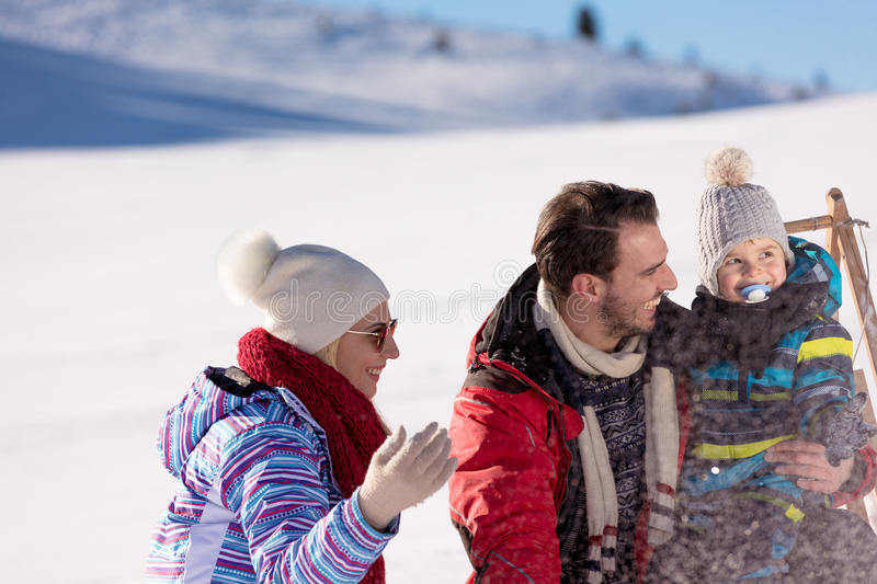 Parenthood, fashion, season and people concept - happy family with child on sled walking in winter outdoors.  stock photos