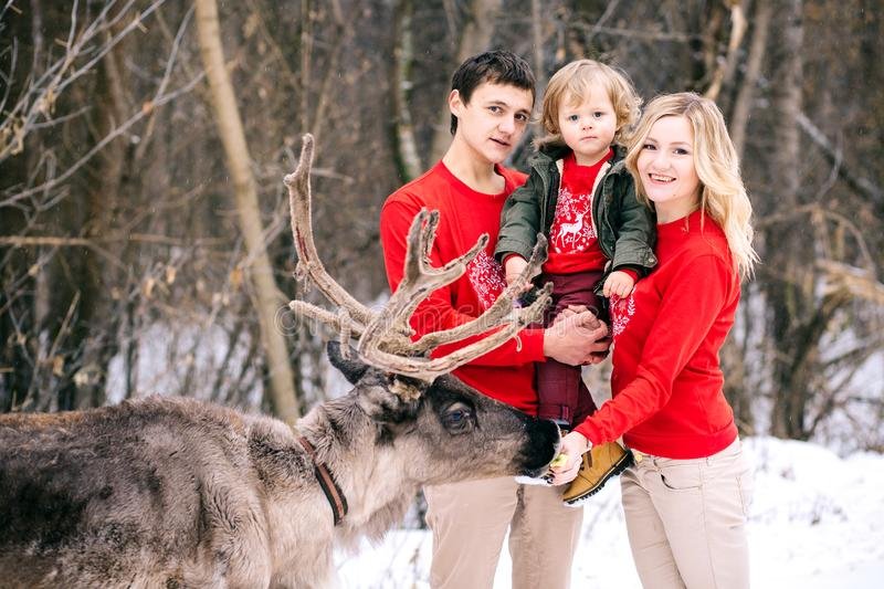 Parenthood, fashion, season and people concept - happy family with child in winter clothes outdoors. New year, Christmas, holiday, winter, family, happiness royalty free stock images