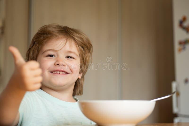 parenthood Peu garçon - concept de nourriture d'écologie Portrait du bel enfant prenant le petit d?jeuner ? la maison Ration d'?t photo libre de droits