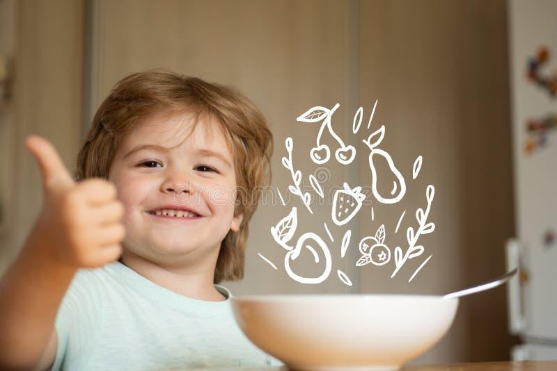 parenthood Peu garçon - concept de nourriture d'écologie Portrait du bel enfant prenant le petit d?jeuner ? la maison Ration d'?t photographie stock libre de droits