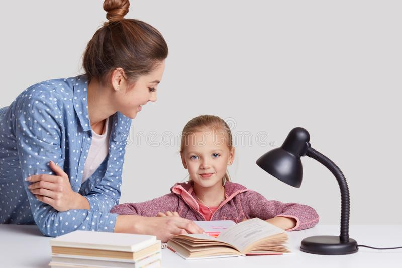 Parenthood, studying and education concept, Attractive blue eyed female child sits at workplace, reads book together with mother, royalty free stock photo