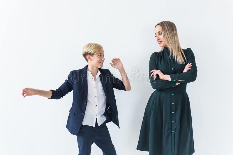 Parenting, family and single parent concept - A happy mother and teen son dancing on white background. Parenting, family and single parent concept - A happy stock photography