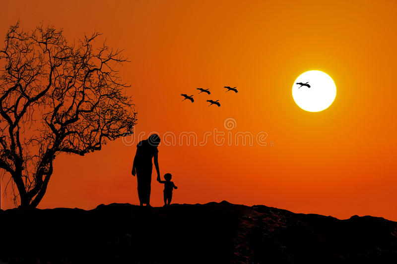 Parenting - Mother and baby silhouette. Mother and baby walking down sunset and storks flying from the tree towards sun. parenting family love bond unity