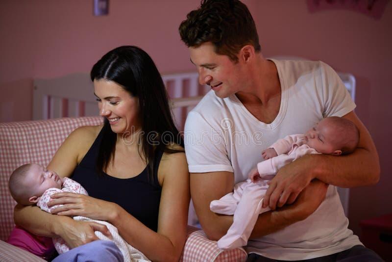 Parents à la maison caressant les filles jumelles de bébé dans la crèche photos stock
