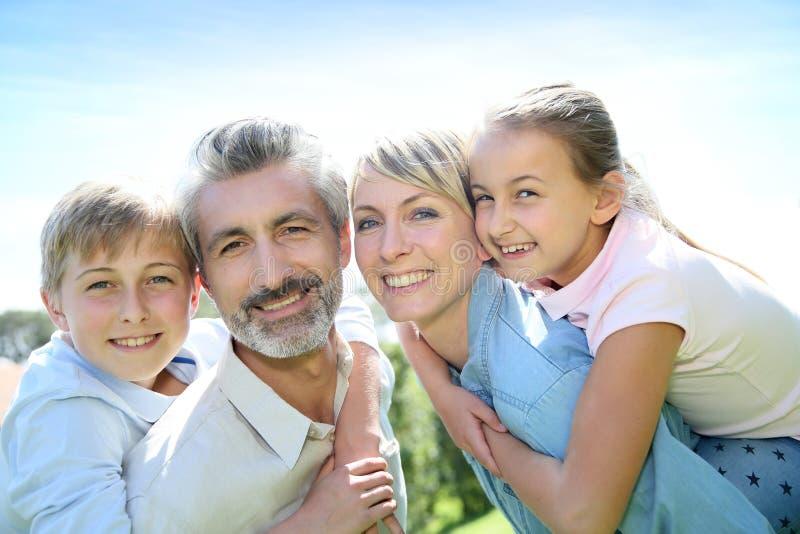 Parents дети нося на их задней части стоковая фотография
