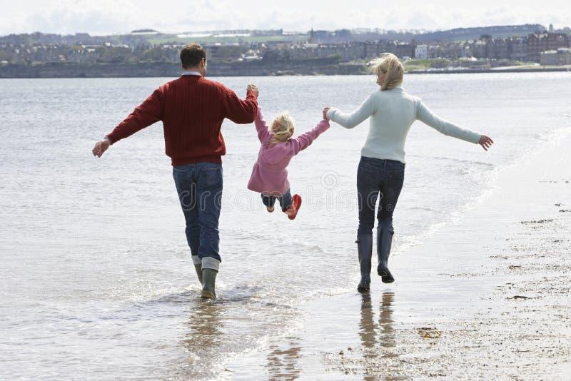 Parents поднимаясь дочь пока идущ вдоль пляжа стоковое фото rf