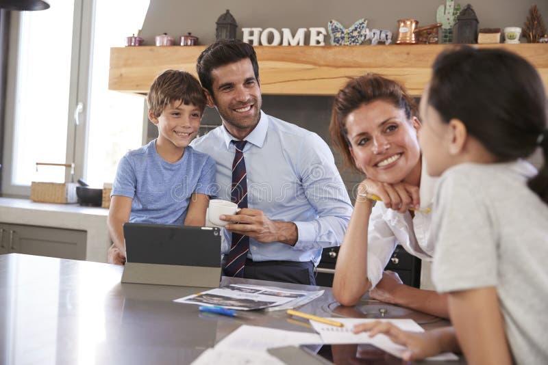 Parents aidant des enfants avec des devoirs avant d'aller travailler photos libres de droits