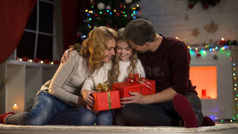 Parents aimants donnant à peu de fille enthousiaste des présents de Noël, tradition de famille photos libres de droits