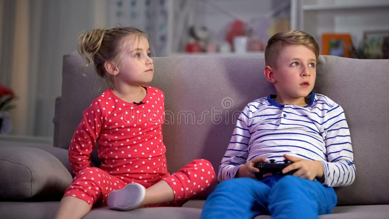Parents attrapant des enfants jouant le jeu la nuit, contr?le de discipline, comportement photo libre de droits