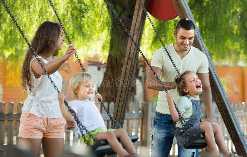 Parents avec des enfants aux oscillations photographie stock