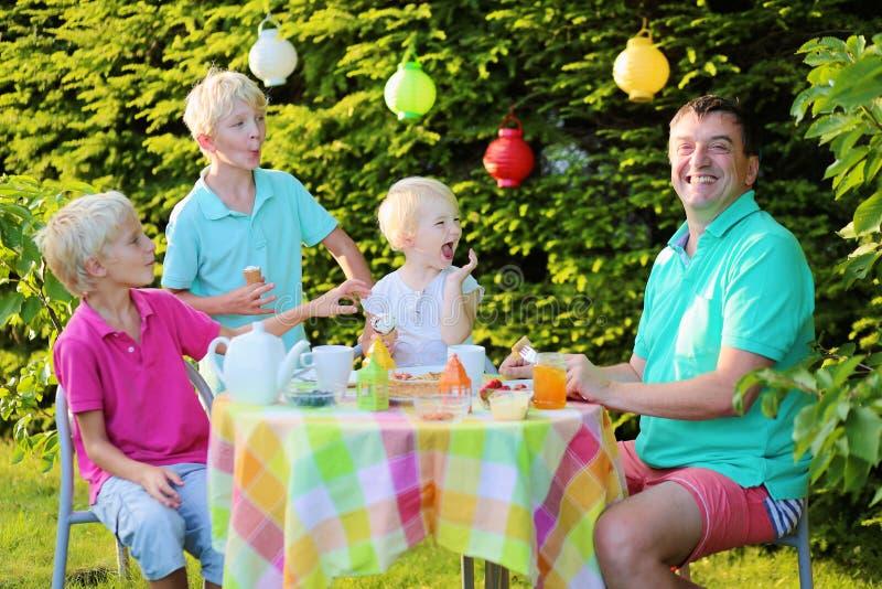 Parents avec des enfants prenant le déjeuner dehors image stock