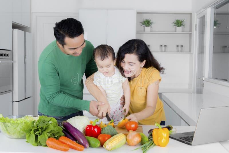Parents avec la fille faisant cuire à la maison photo libre de droits