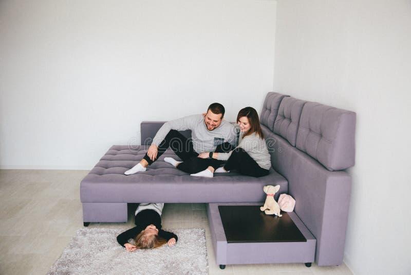 Parents avec la petite fille riant dans la chambre image stock