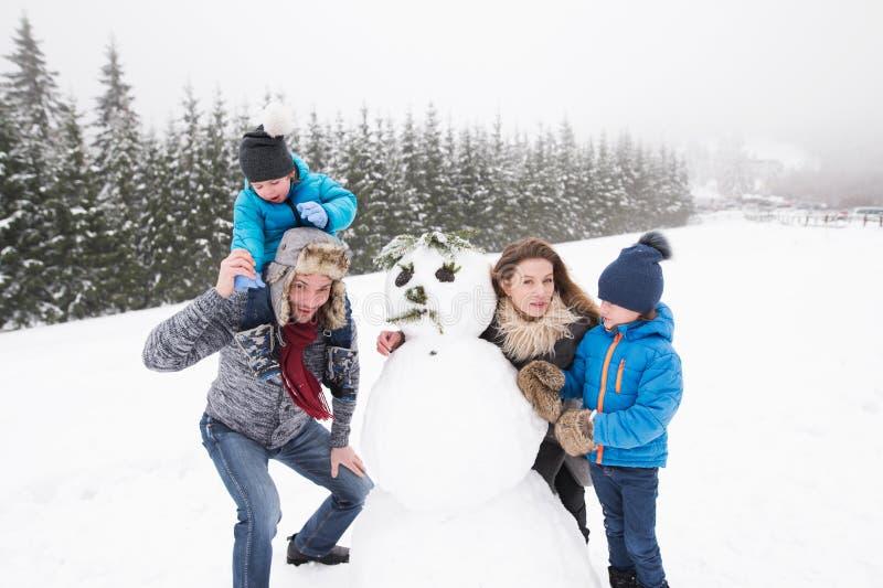 Parents avec leurs fils, jouant dans la neige, bonhomme de neige de construction photos libres de droits
