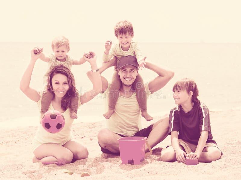 Parents avec trois enfants sur la plage photo stock