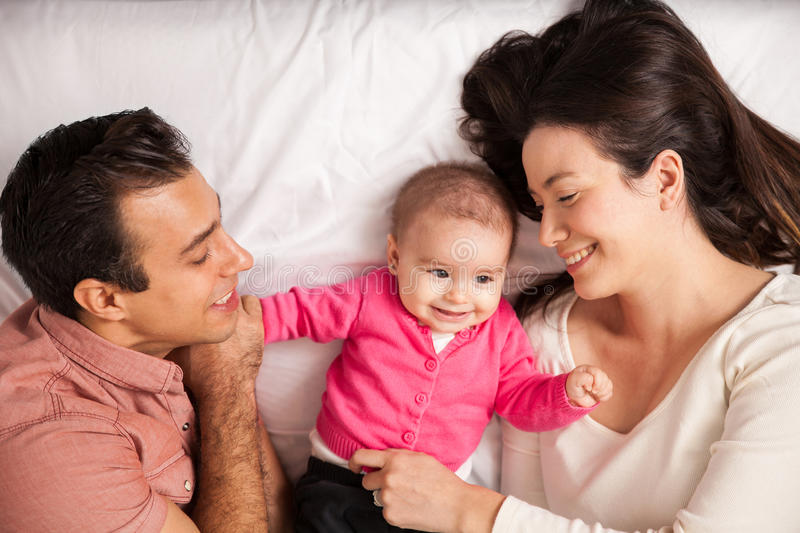 Parents and baby in a bed. Beautiful happy couple and their baby relaxing in a bed together royalty free stock photos
