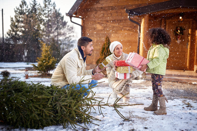 Parents with black daughter bringing boxes with Christmas gifts royalty free stock photography