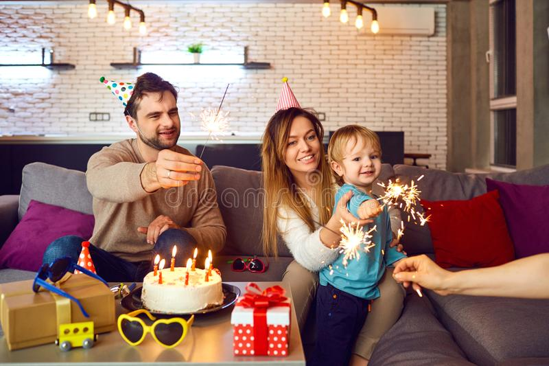 Parents with a cake congratulate their child on his birthday. stock photos