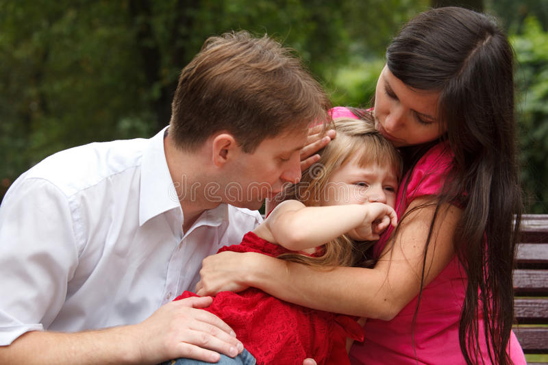 Parents calm crying girl on walk in summer garden. Mum embraces daughter. Close up stock images