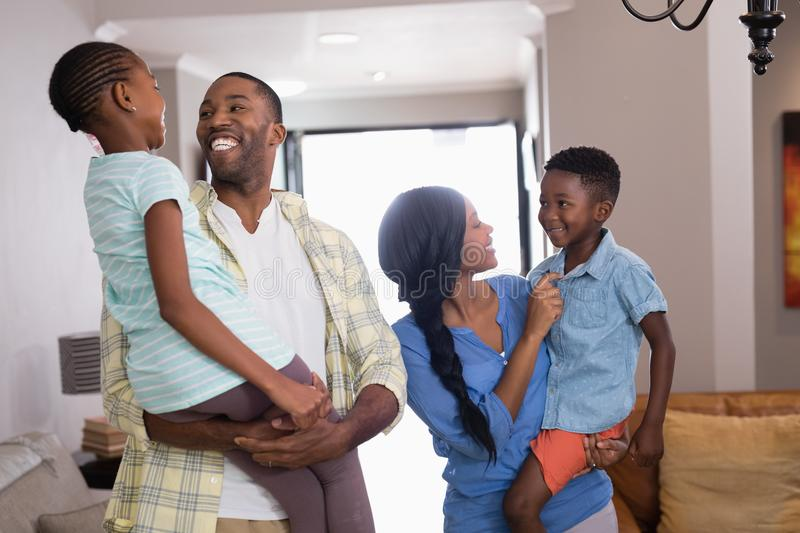 Parents carrying children in living room at home royalty free stock photos
