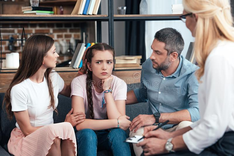 Parents cheering up daughter on therapy session by female counselor. In office stock images
