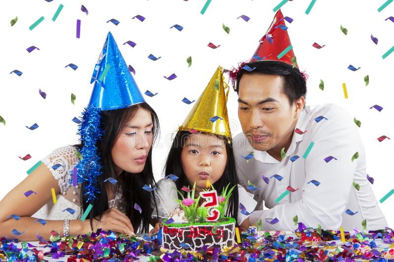 Parents and child blowing out birthday candles stock image