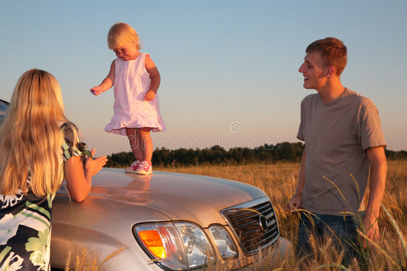 Parents and child on car cowl on wheaten field stock photography
