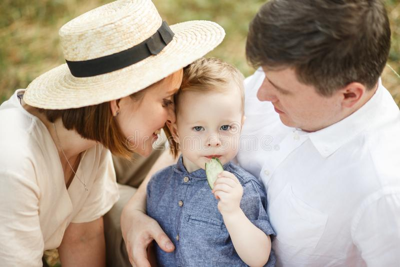 Parents with the child sit in the park. They look at him. The kid looks straight and eats royalty free stock image