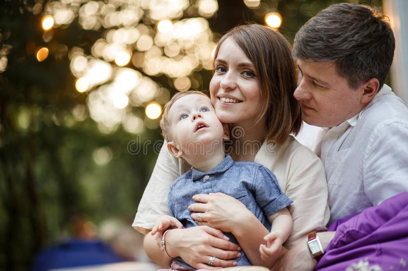Parents with a child are sitting in a park. The kid looks up royalty free stock photos
