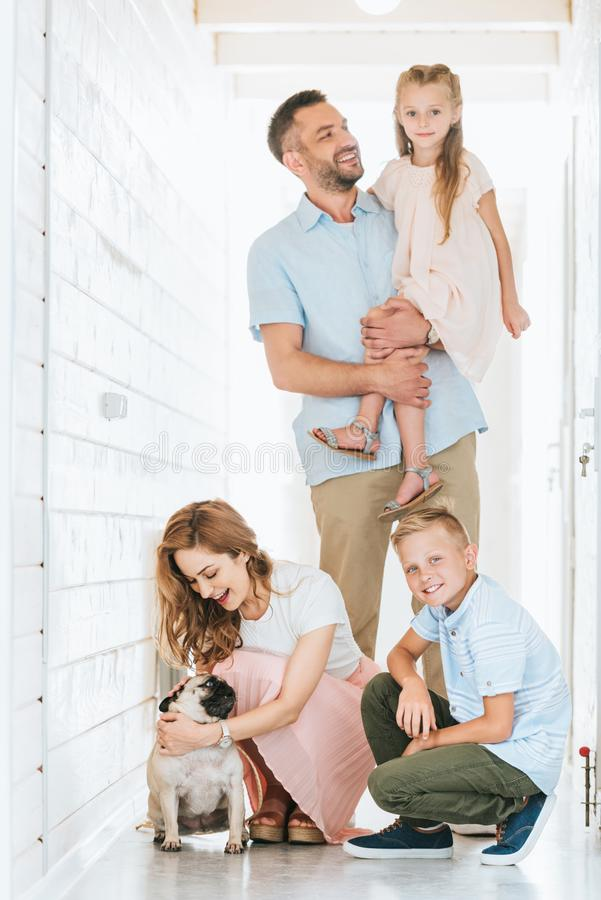 Parents and children with adopted pug dog at animals. Shelter royalty free stock photo