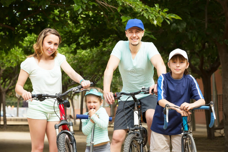 Parents with children with bicycles. Parents with children staying with bicycles in park and smiling royalty free stock photography