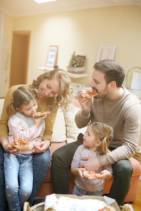 Parents and children eating pizza together. Happy family enjoying in meal together at home. royalty free stock photography