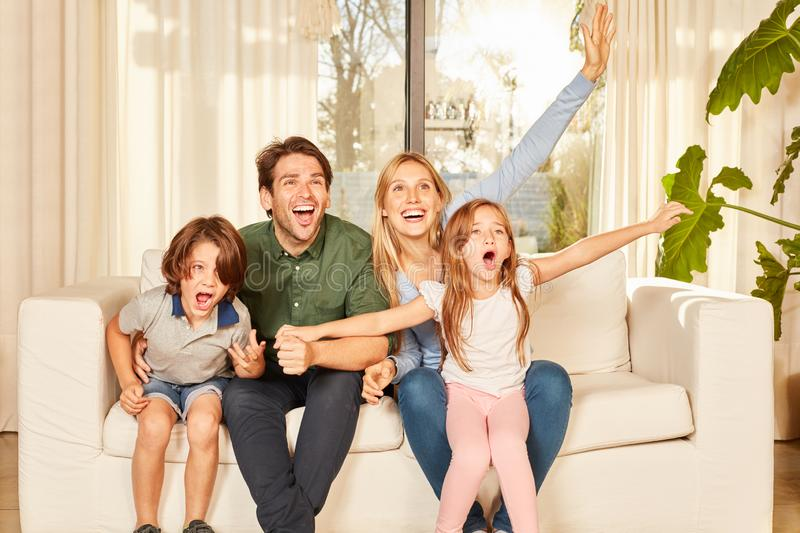 Parents and children cheerfully rejoice on the sofa stock images